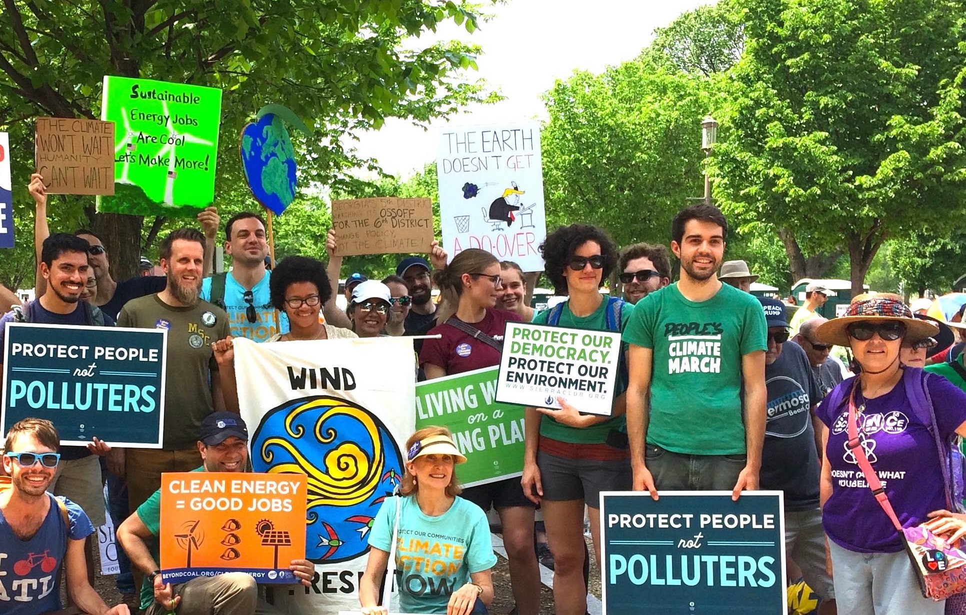 A diverse group of Sierra Club activists holding signs in support of clean energy solutions.